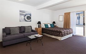 flatscreen TV and two-seater sofa in the room