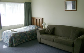 single bed and a couch in the lounge