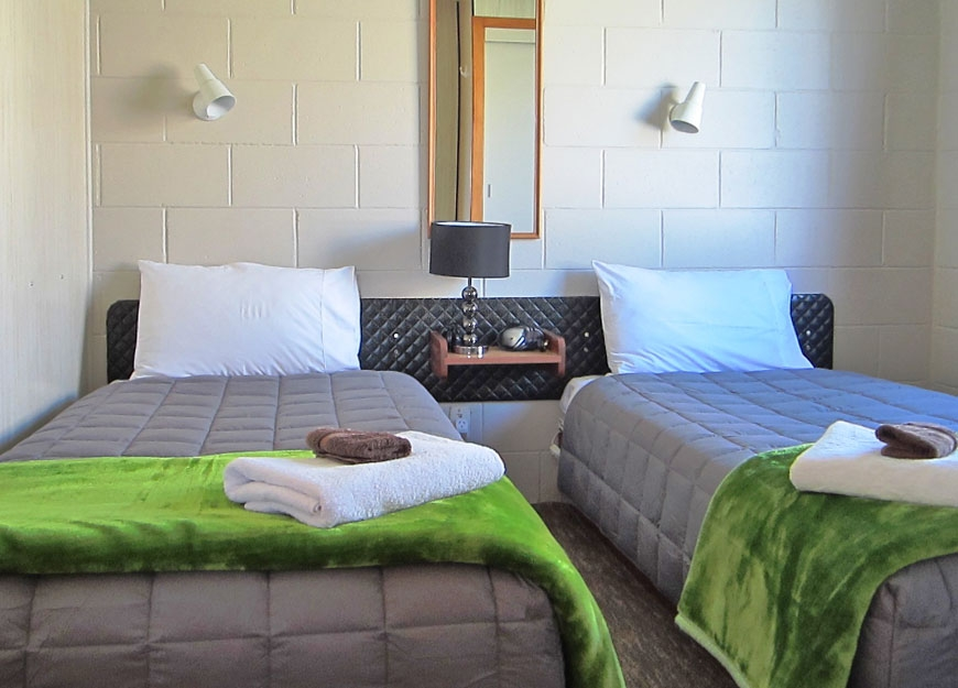 room of a 2-bedroom unit has two single beds