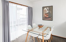 a queen-size and a single bed in the lounge of 1-bedroom unit