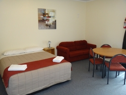 queen bed, a sofa and dining table in the lounge