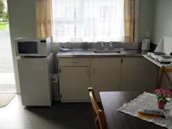 kitchen with full stove, fridge and microwave