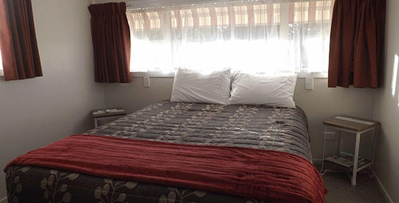a queen-size bed in the main bedroom of 2-bedroom unit