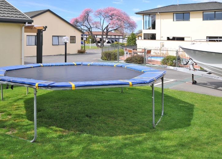 playground has a trampoline, swing and slide