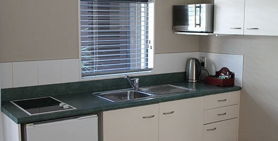 kitchenette with microwave, fridge and benchtop elements