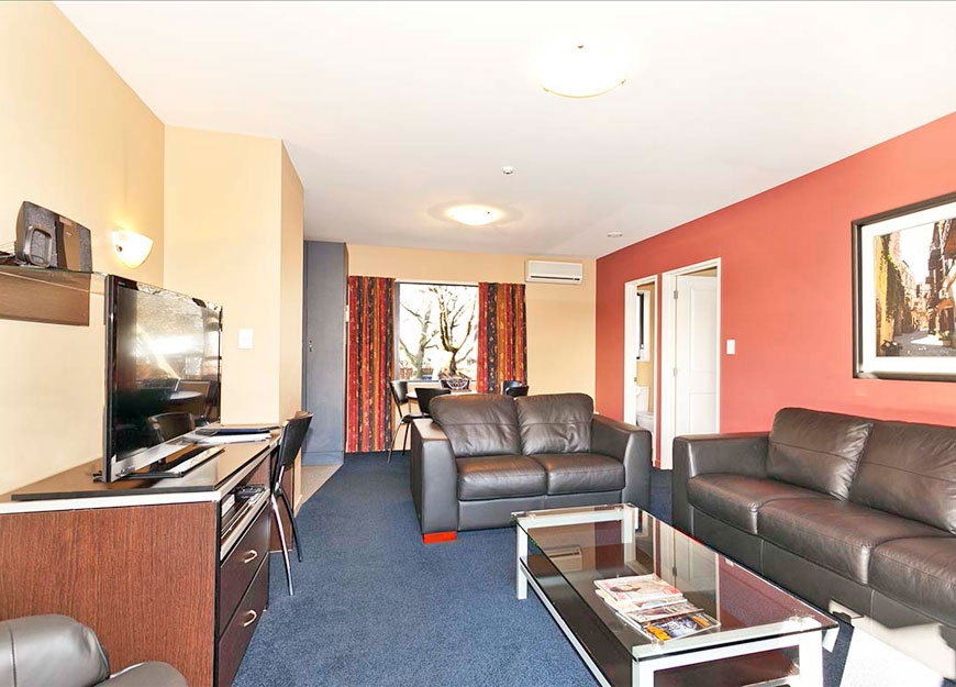 spacious lounge with comfortable sofas and 40-inch LED TV