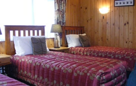 three single beds in the lounge of Pine Cottage