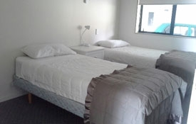 two single beds in a room of two bedroom unit
