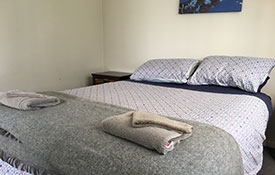 queen-size bed in the main room of 2-bedroom motel unit