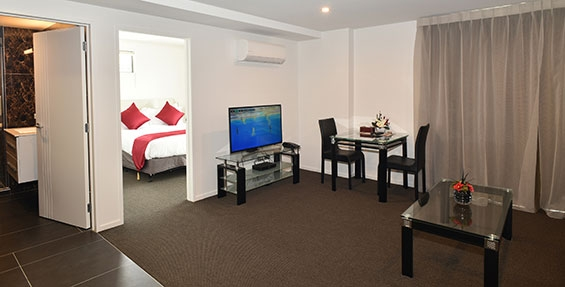 spacious lounge with comfortable couch, dining table and flatscreen smart TV