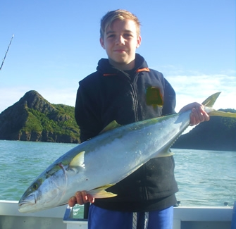 Image of a boy holding a large fish he has caught in the Bay of Islands