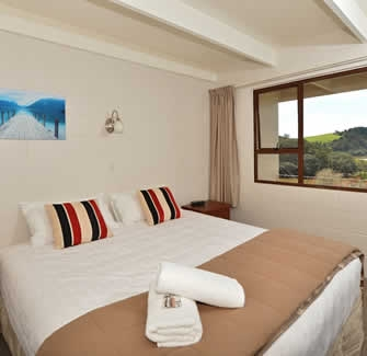 Image of a king bed in a 2-bedroom ground floor motel unit at Falls Motel in Paihia
