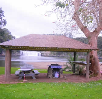 Image of the sheltered BBQ area in the Paihia Waterfront Campground with Haruru Falls in the background